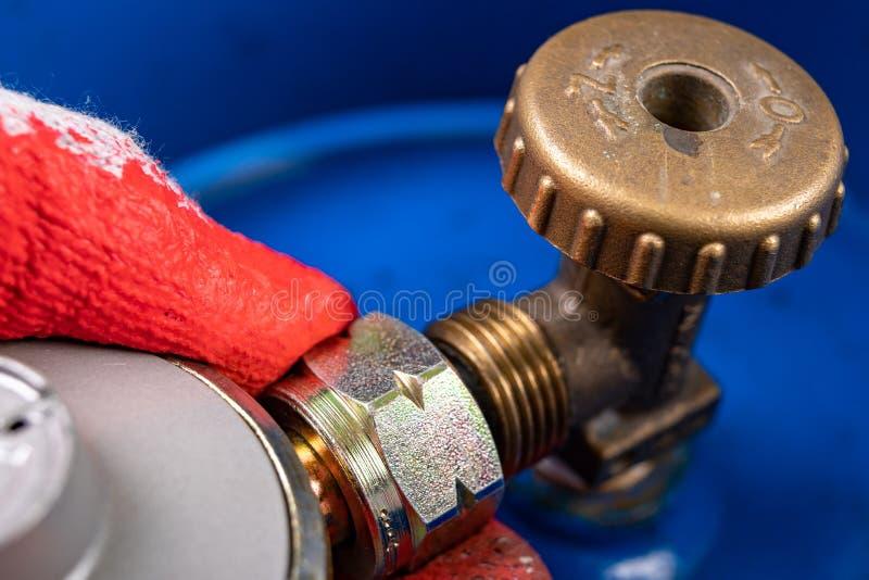 Cilindro del reductor y de gas para el uso nacional Reemplazo del cilindro de gas en la cocina casera foto de archivo