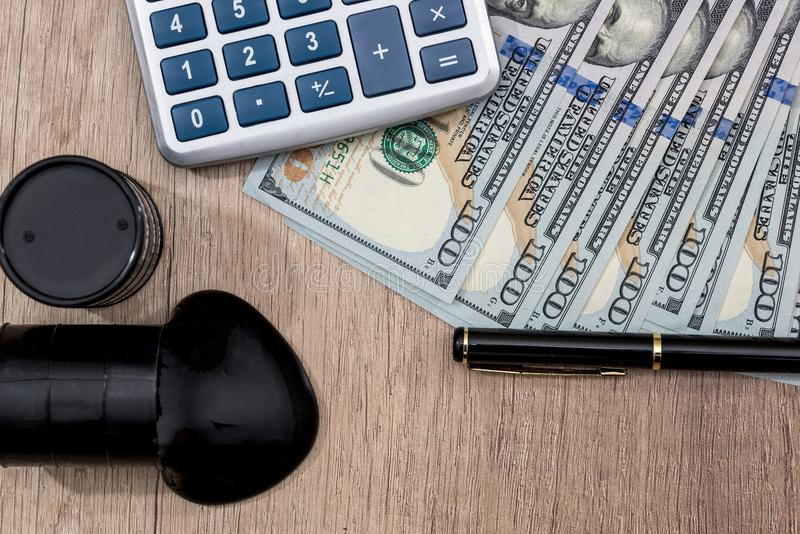 Cilindros de óleo em dólares americanos com calculadora fotografia de stock royalty free