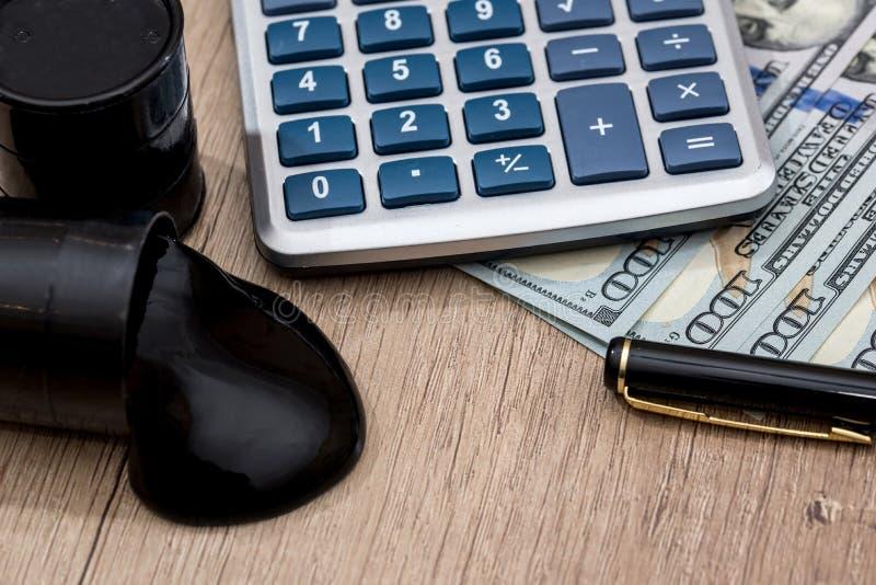 Cilindros de óleo em dólares americanos com calculadora imagem de stock