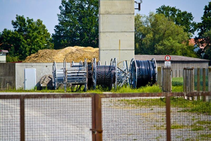 Cilindros de cabo elétrico perto de um central nuclear desarmado em Baviera, Alemanha fotografia de stock