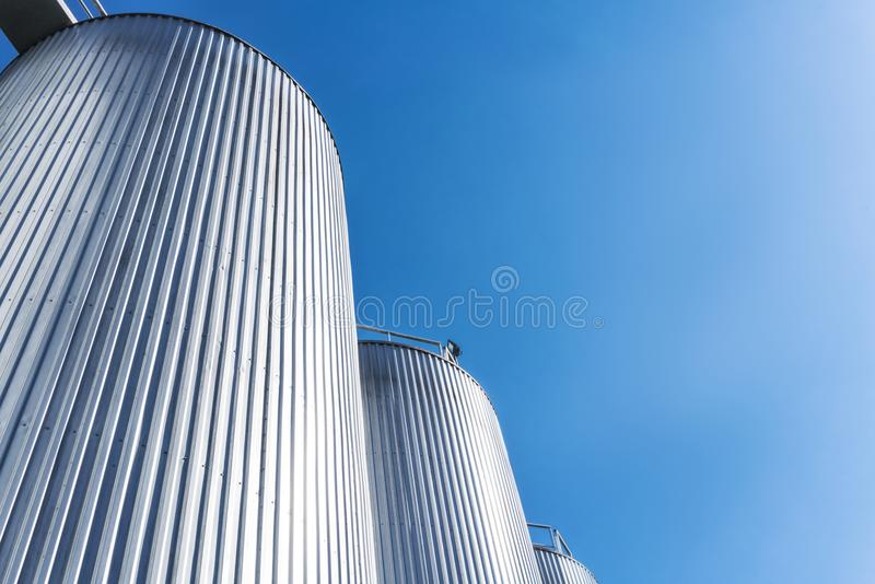 Cilindros de la fábrica de la bebida Con el cielo azul imagen de archivo