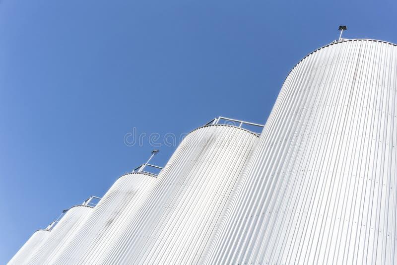 Cilindros de la fábrica de la bebida Con el cielo azul imagenes de archivo