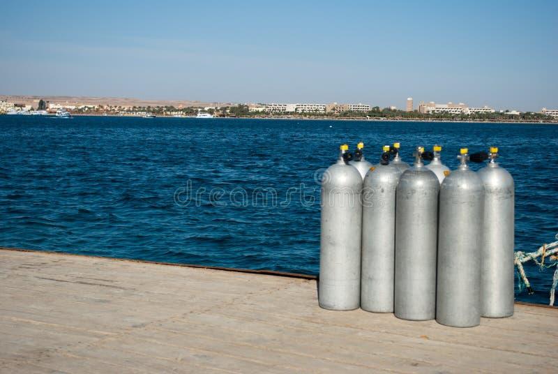 Cilindros do grupo oito com ar oito cilindros de alumínio na doca do mar Oceano azul e cilindros de aço brancos imagens de stock royalty free