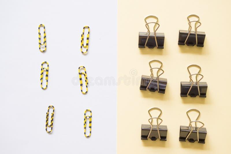 Cilp negro del papel en el fondo blanco y el fondo amarillo fotos de archivo libres de regalías