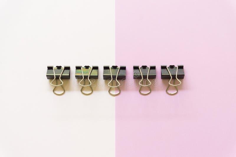 Cilp negro del papel en el fondo blanco y rosado fotografía de archivo
