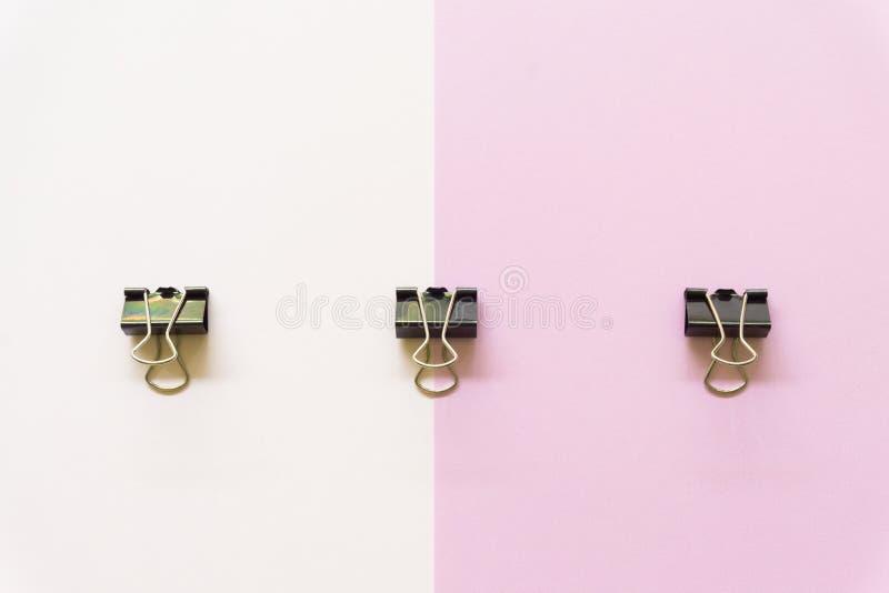Cilp negro del papel en el fondo blanco y rosado fotos de archivo