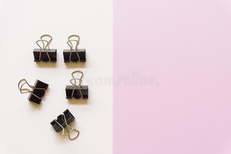 Cilp negro del papel en el fondo blanco y rosado fotos de archivo libres de regalías