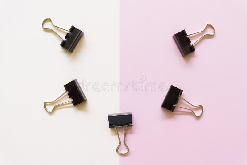 Cilps negros del papel en el fondo blanco y rosado fotos de archivo