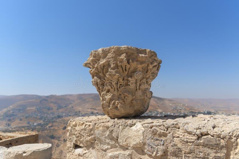 Cima antica della colonna romana, posizionata sul resti antico di vecchia città del crociato di Kerak Giordania, contro un cielo  immagine stock libera da diritti