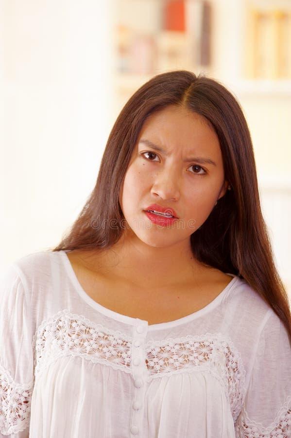 Cima bianca d'uso della blusa della bella giovane donna castana, affrontante macchina fotografica che interagisce, fondo luminoso immagine stock
