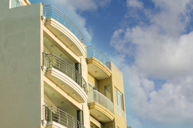 Cima della costruzione del yelow con i balconi di vetro nella baia Malta di St Paul, con cielo blu con le nuvole fotografia stock