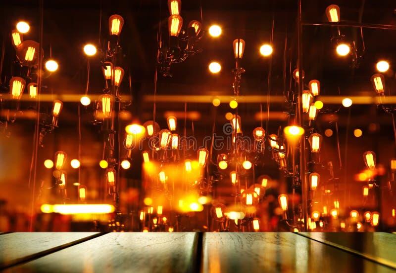 Cima della tavola di legno con la lampada arancione-chiaro della sfuocatura della barra o del pub per immagine stock libera da diritti