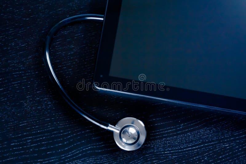 Cima della vista dello stetoscopio medico vicino al pc digitale moderno della compressa in laboratorio sulla tavola di legno immagini stock