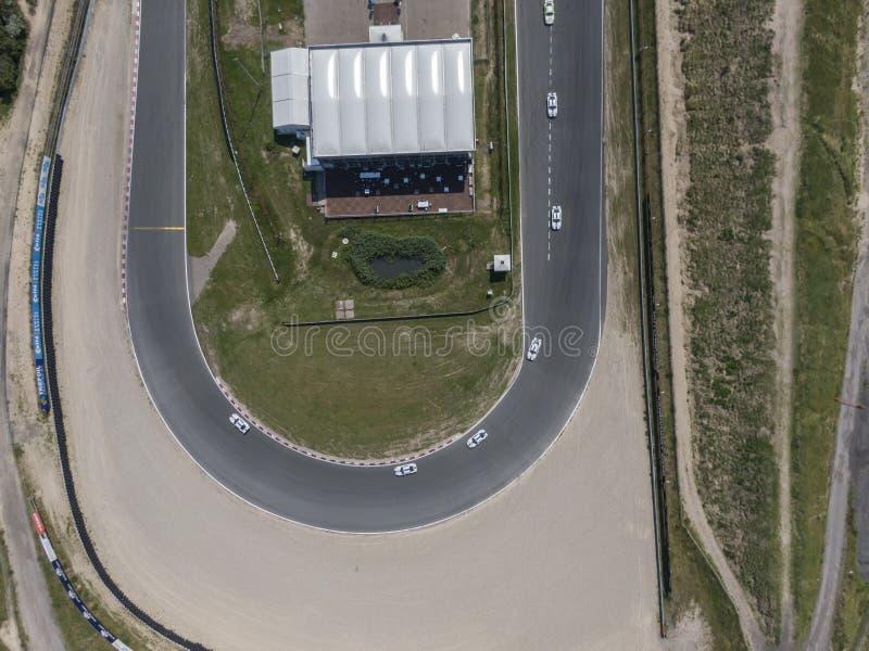 Cima giù la vista aerea della curva in circuito di pista della corsa di sport di motore con il bordo della strada della sabbia fotografie stock
