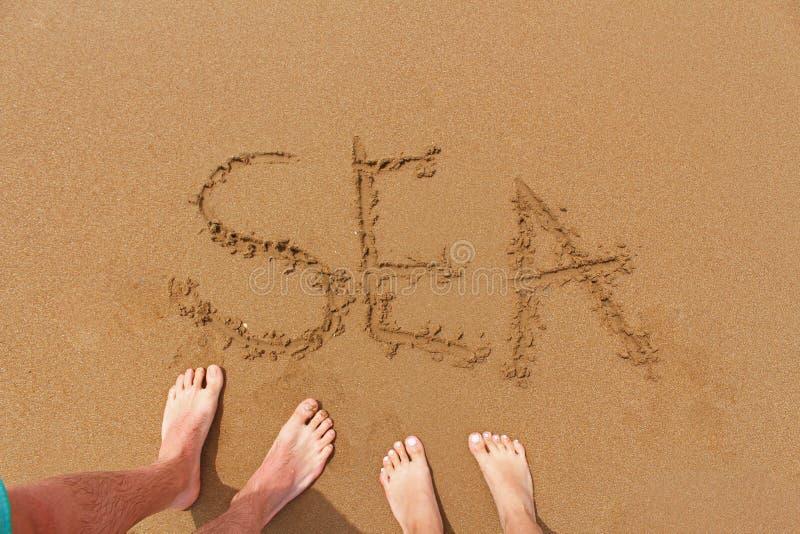 Cima giù la vista dei piedi femminili e maschii nella sabbia sulla spiaggia Scrittura del mare su una spiaggia Concetto di viaggi immagine stock libera da diritti