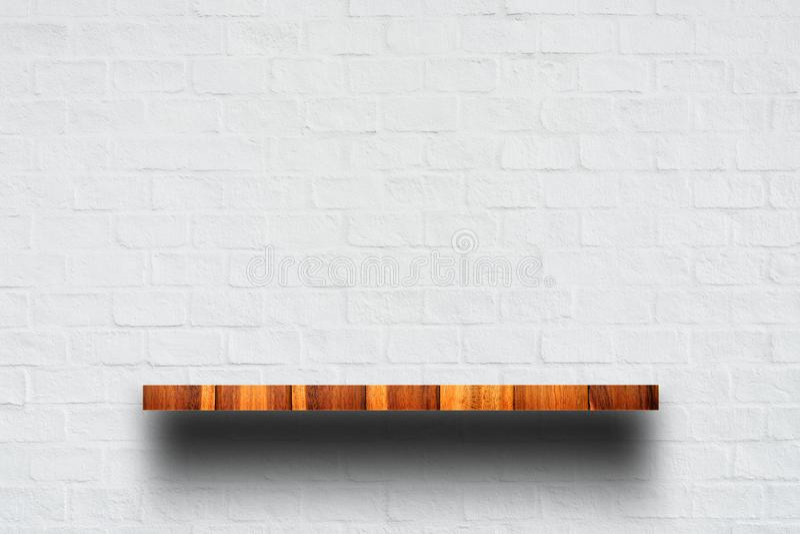 Cima vuota dello scaffale di legno con il muro di mattoni bianco immagine stock
