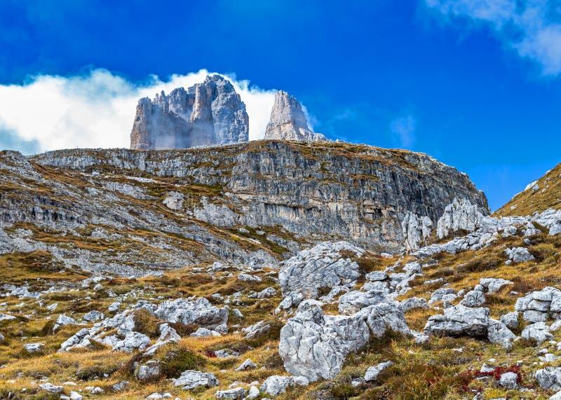Cimeira de três picos atrás da cara da rocha fotografia de stock
