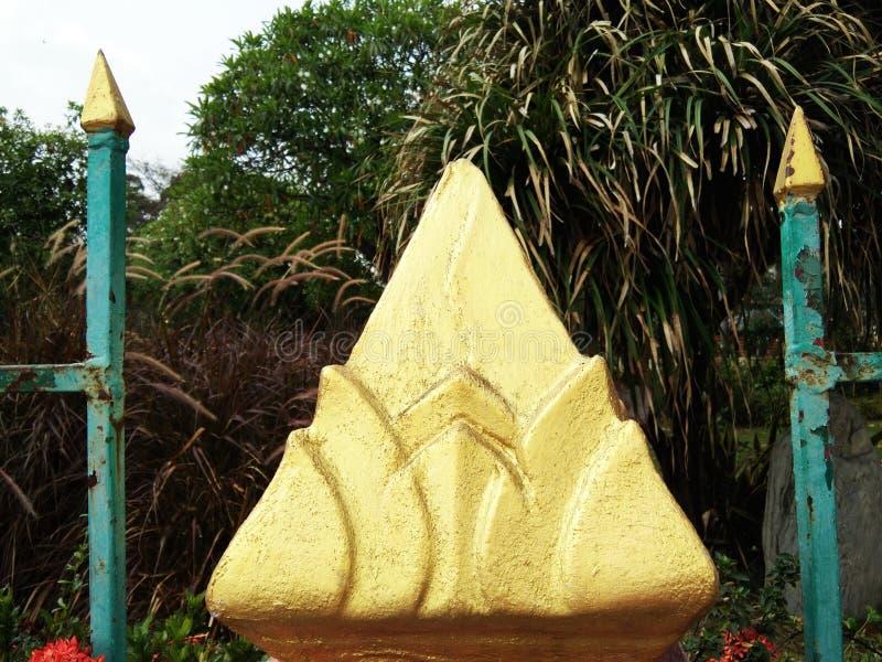 Ciment d'or de fleur de lotus artificiel entre les poteaux en acier bleus rouillés images stock
