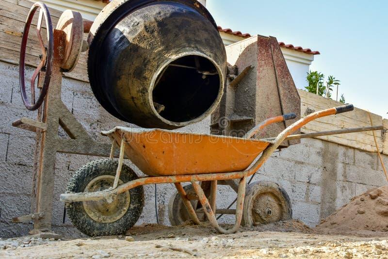 Cimente a fatura para o trabalho da construção, com a máquina do moinho do cimento e o carrinho de mão imagem de stock