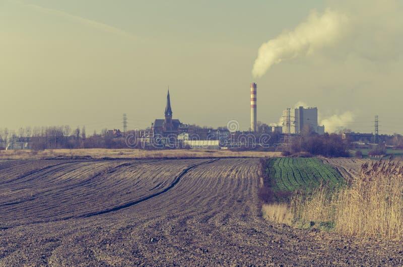 Ciminiera di fumo di una centrale elettrica vicino ad un campo dell'azienda agricola fotografia stock libera da diritti