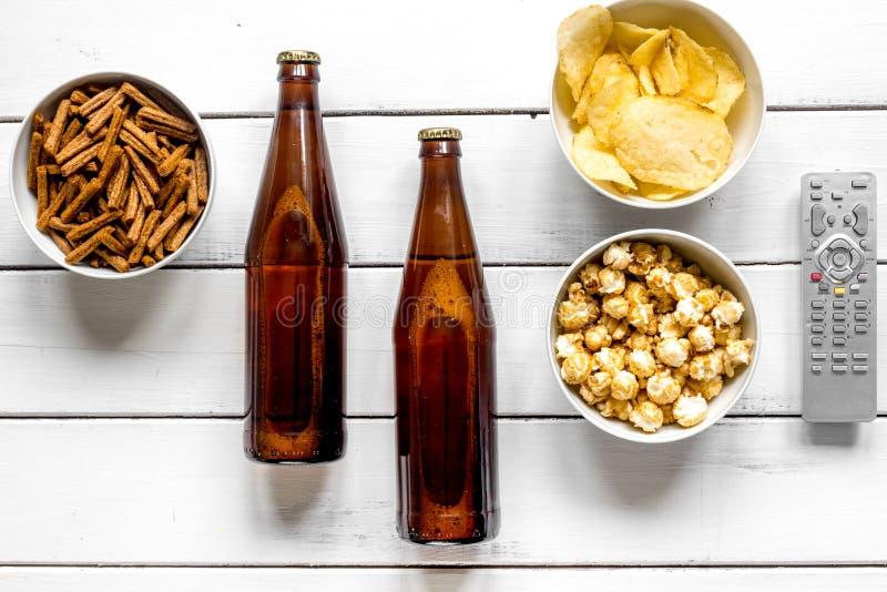 Cinéma et TV whatching avec de la bière, des miettes, des puces et la vue supérieure de fond en bois blanc de maïs de bruit images libres de droits