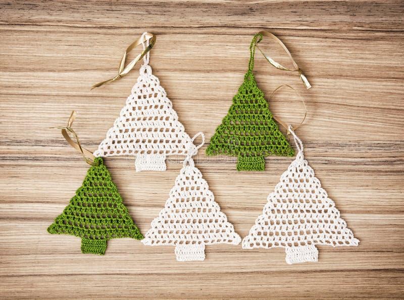 Cinco árboles de navidad del ganchillo en el fondo de madera fotos de archivo
