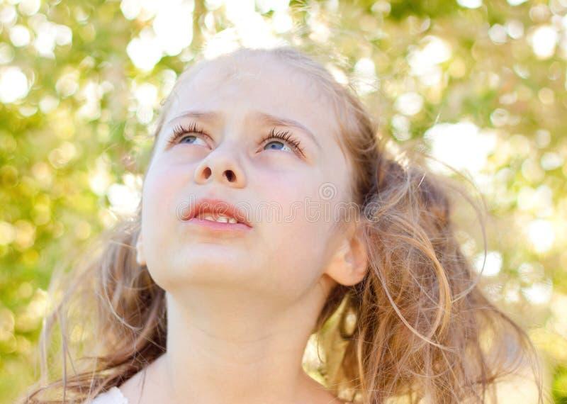 Cinco años de la muchacha caucásica del niño en el jardín que mira para arriba imagen de archivo libre de regalías