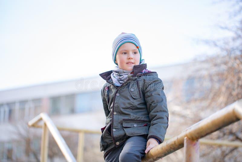 Cinco años del muchacho en casquillo que sonríe en paisaje del otoño imágenes de archivo libres de regalías