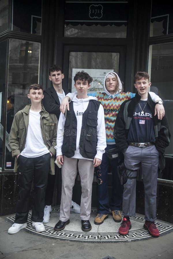 Cinco amigos adolescentes estão estando fora da costa fotografia de stock
