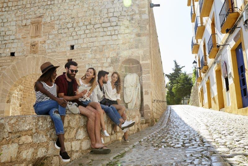 Cinco amigos el día de fiesta que se sienta en una pared en Ibiza fotos de archivo libres de regalías