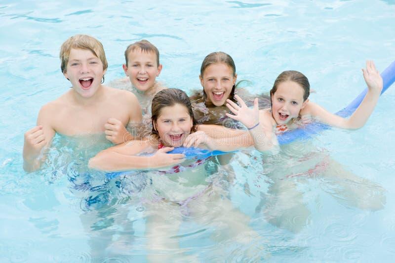 Cinco amigos jovenes en jugar de la piscina imágenes de archivo libres de regalías
