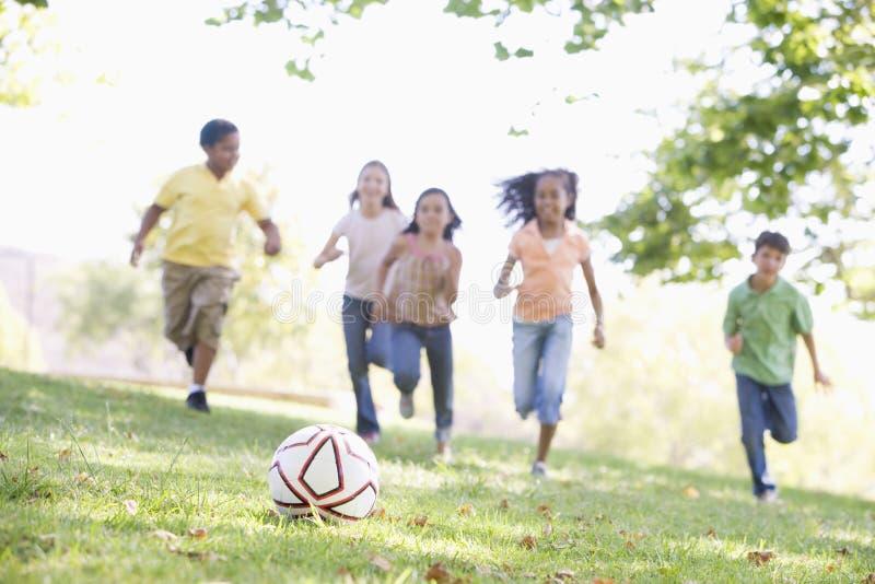 Cinco amigos jovenes que juegan a fútbol fotografía de archivo