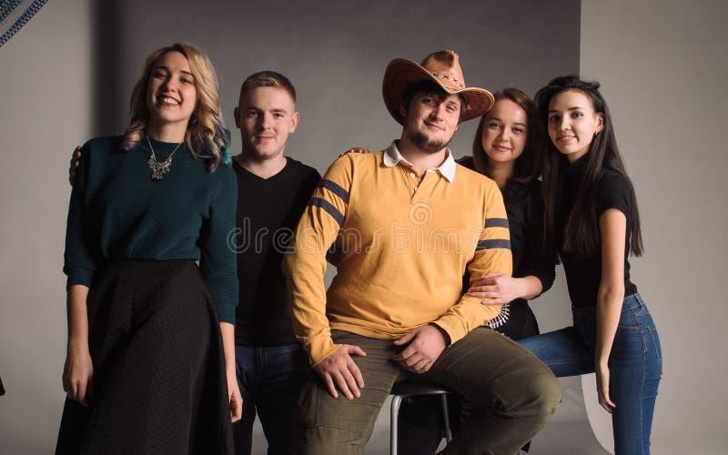 Cinco amigos novos frescos que estão junto e que sorriem O estúdio disparado na parede cinzenta fotos de stock