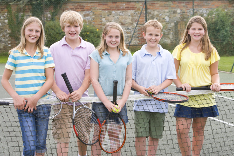 Cinco amigos novos no sorriso da corte de tênis fotografia de stock royalty free