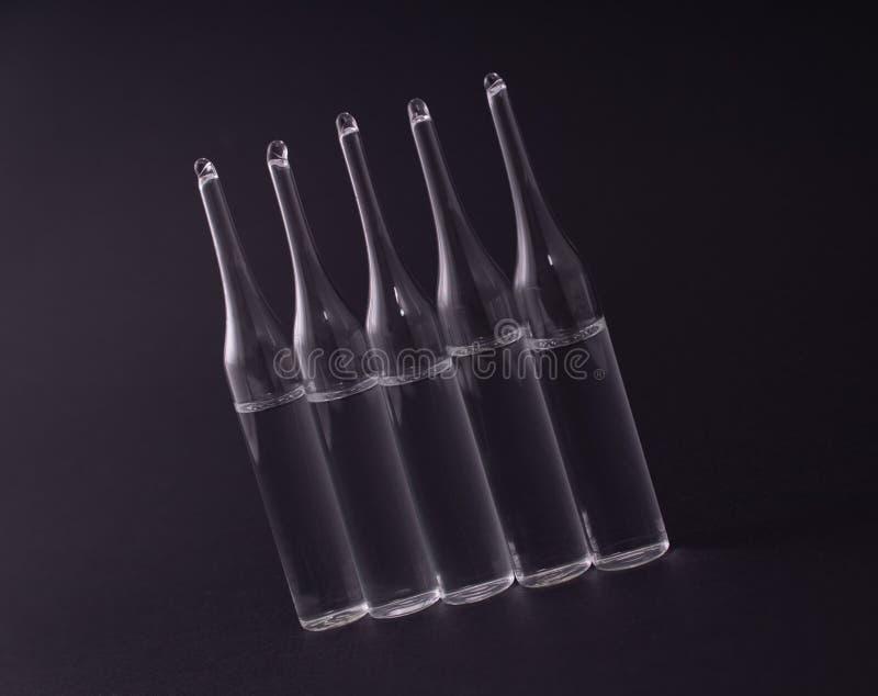 Cinco ampollas en fila en un fondo negro imagen de archivo