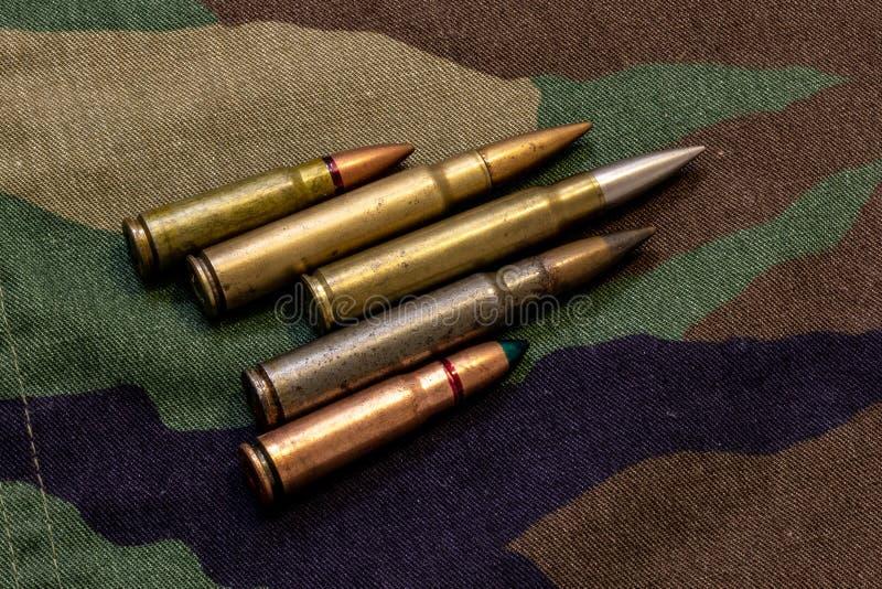 Cinco balas del rifle en la capa militar del camuflaje en el fondo fotografía de archivo