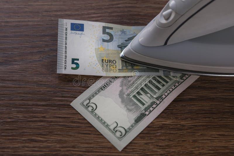 Cinco billetes de banco del dólar y del cinco-euro debajo del hierro en la tabla de madera foto de archivo