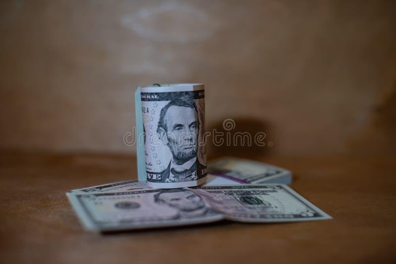 Cinco billetes de dólar en un rollo que miente en un paquete de billetes de banco fotografía de archivo libre de regalías