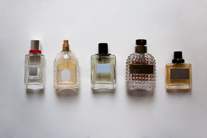 Cinco botellas de perfume de cristal en el fondo blanco desde arriba imagenes de archivo