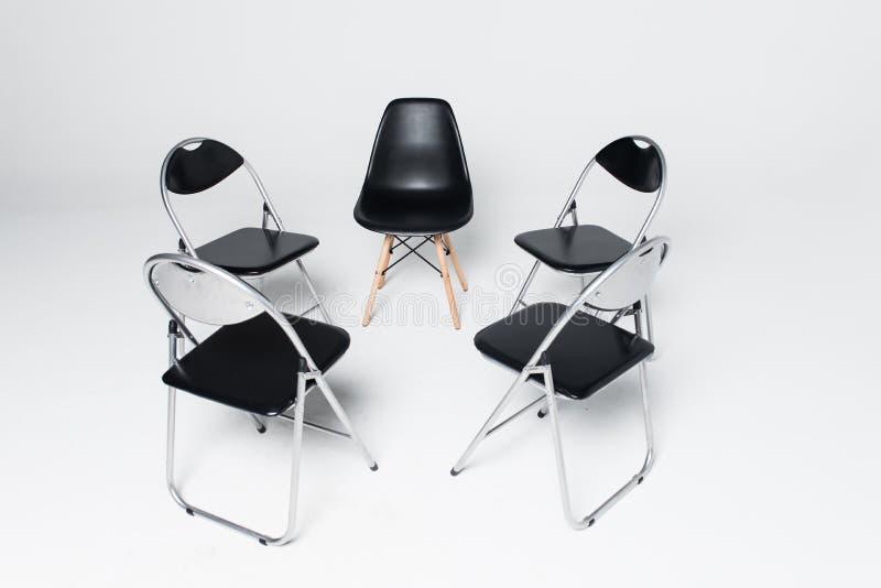 Cinco cadeiras pretas em um círculo isolado no fundo branco imagem de stock royalty free