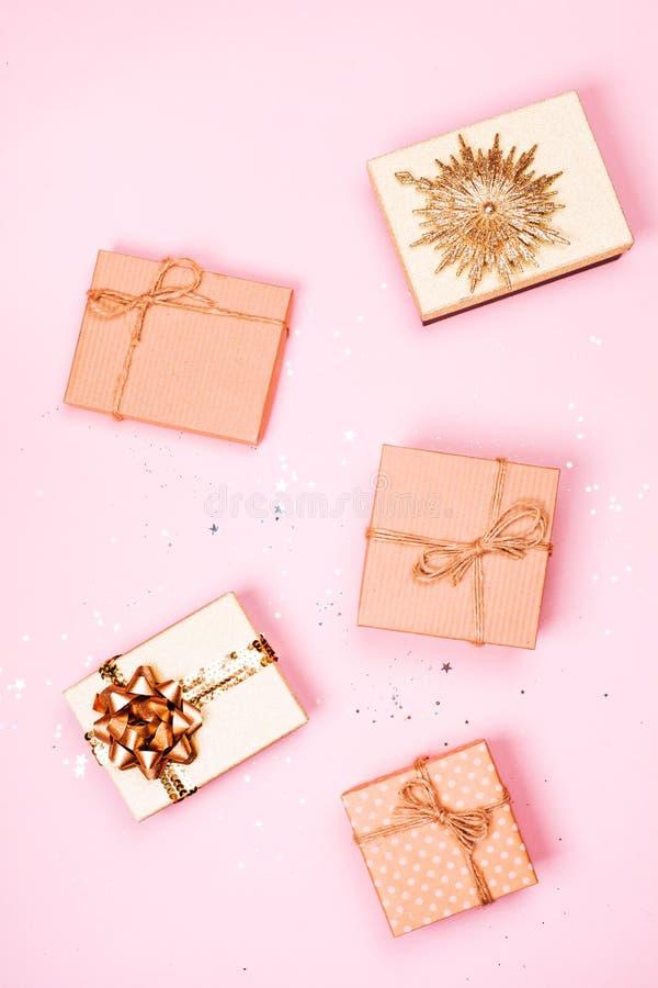 Cinco caixas de presente do ofício do Natal com brilho no fundo pastel cor-de-rosa fotos de stock