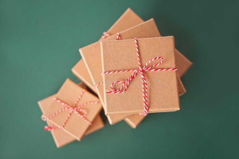 Cinco cajas de regalo de Navidad de diferentes tamaños sobre el fondo verde imagenes de archivo