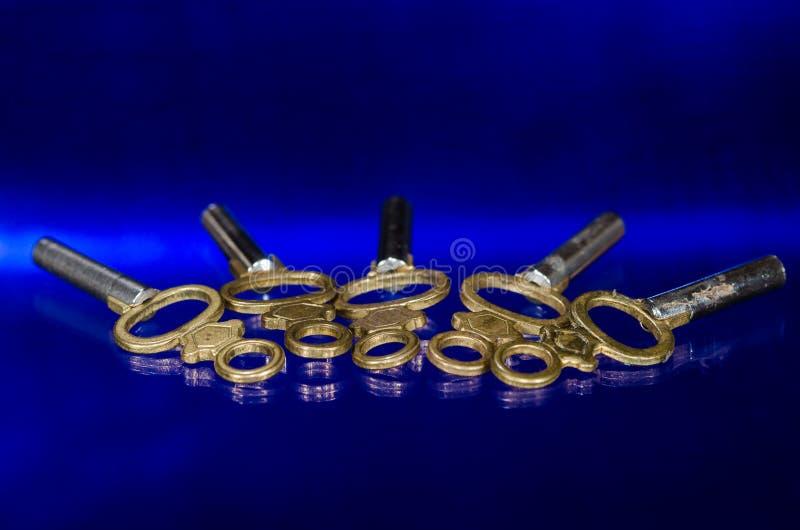 Cinco chaves de relógio de bronze antigas do bolso que colocam na superfície do azul foto de stock royalty free