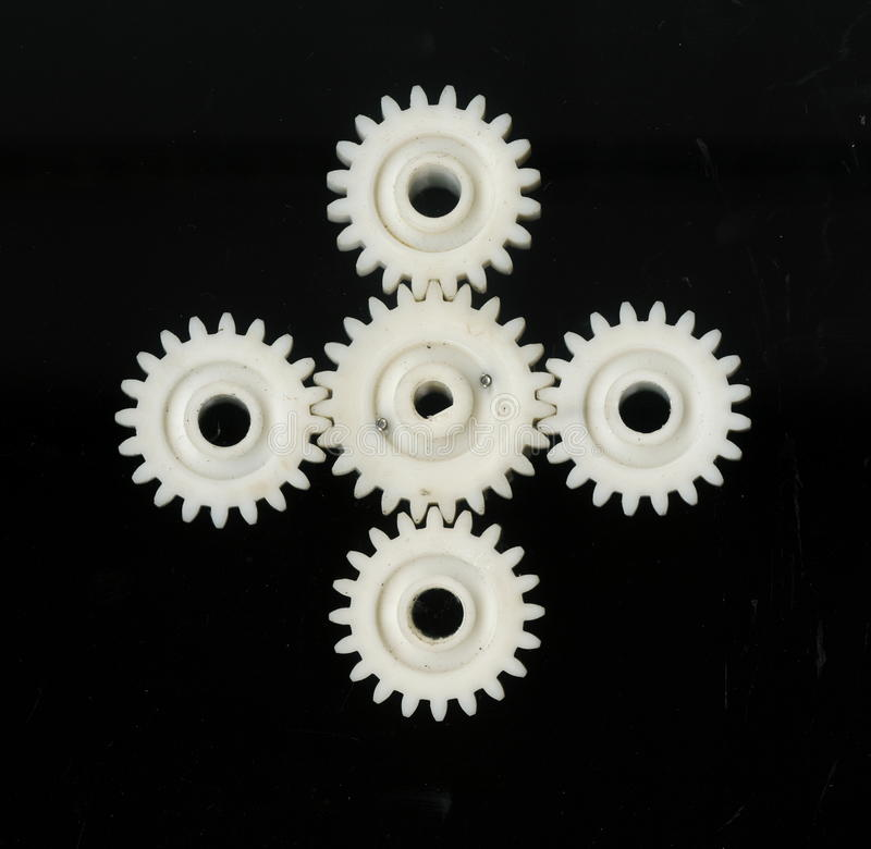 Cinco concatenaram as engrenagens dentadas plásticas brancas de tamanhos diferentes em um fundo preto imagens de stock royalty free