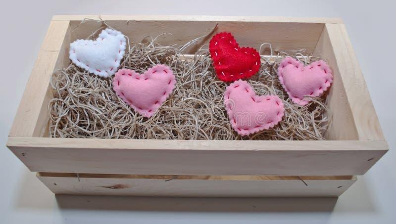 Cinco corações coloridos diferentes de pano em uma caixa de madeira imagem de stock