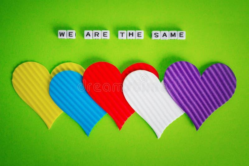 Cinco corazones multicolores de la tarjeta del día de San Valentín y la inscripción que somos lo mismo hicieron de los cubos blan foto de archivo