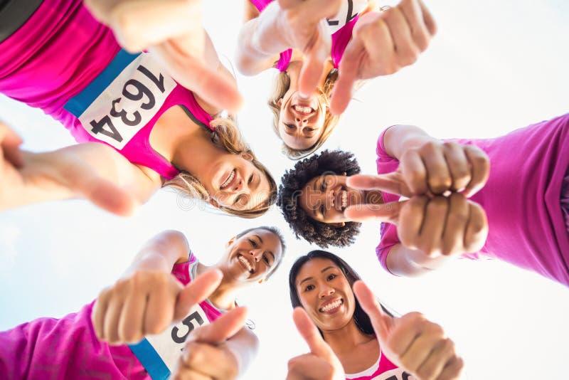 Cinco corredores de sorriso que apoiam a maratona do câncer da mama fotos de stock royalty free