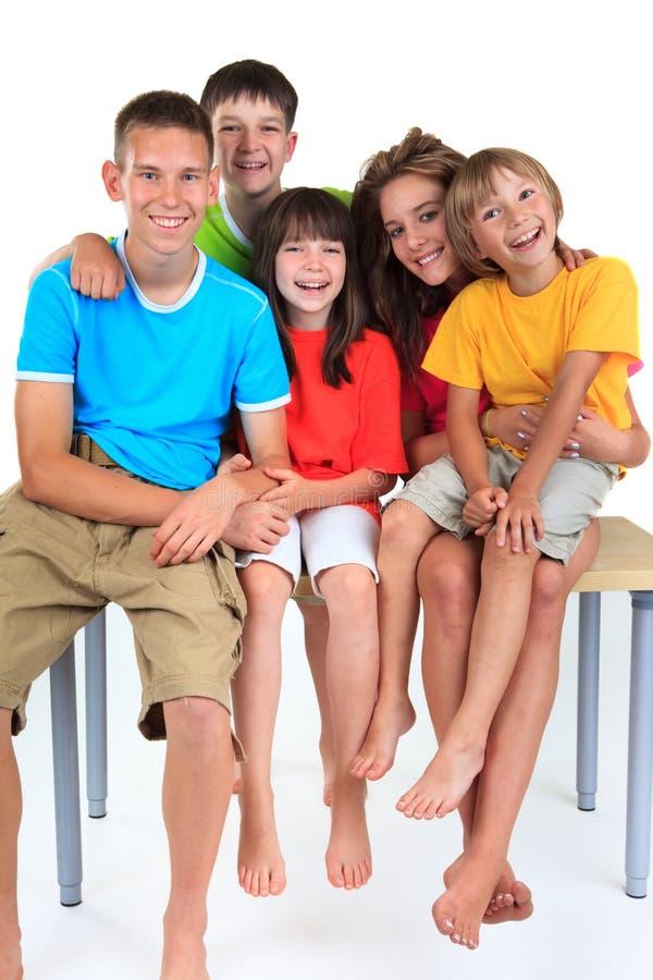Cinco crianças que sentam-se na tabela fotos de stock
