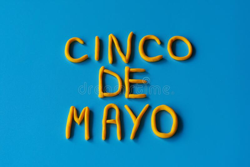 CINCO DE MAYO的词是由蓝色背景上的粘土制成的,平躺的 5月5日,美国,墨西哥假日,背景 免版税库存照片