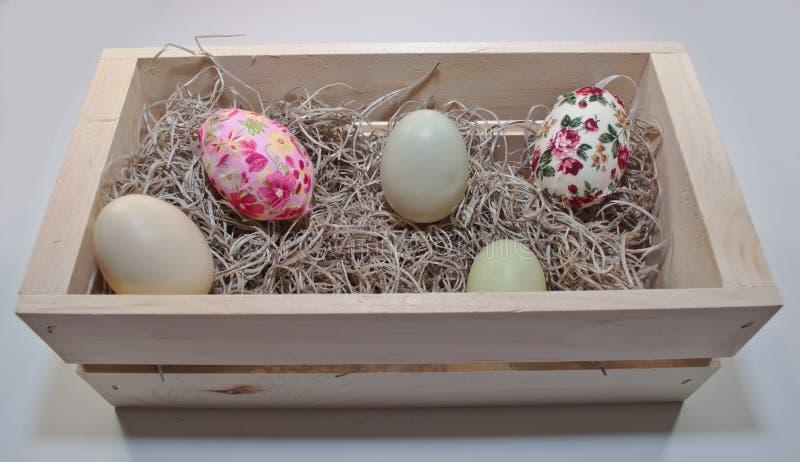 Cinco diversos huevos de Pascua coloreados en una caja de madera imagenes de archivo